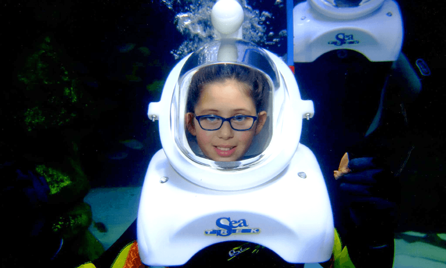 Cute little girl sea trekker with glasses and holding a shark tooth